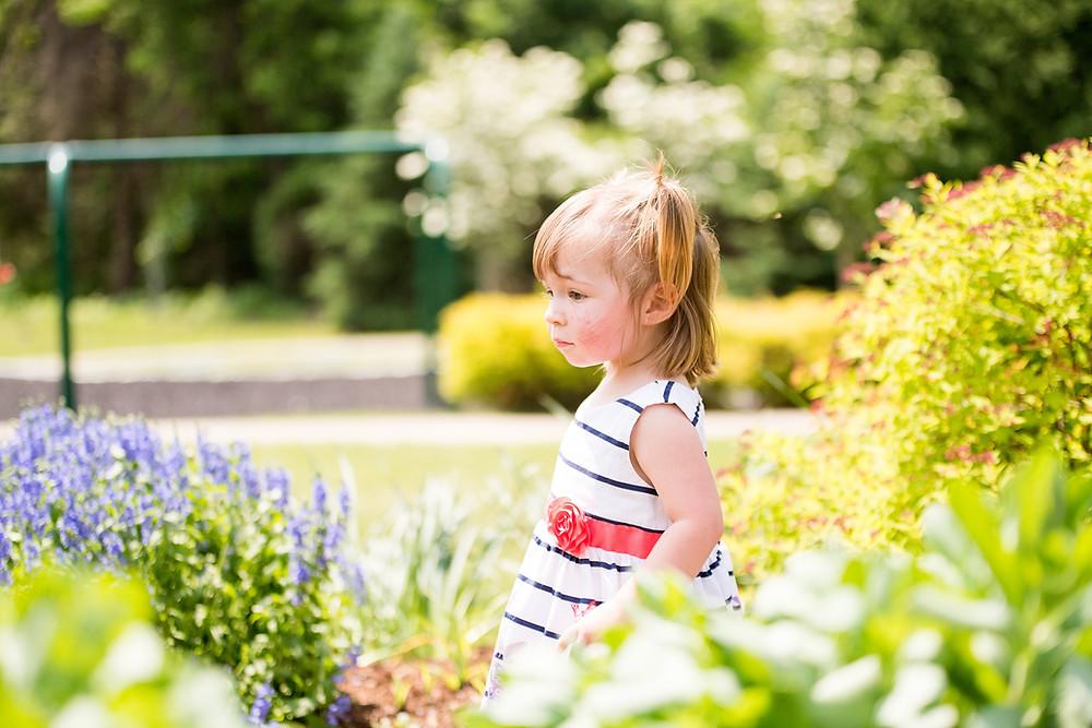 Little girl walks through a beautiful garden