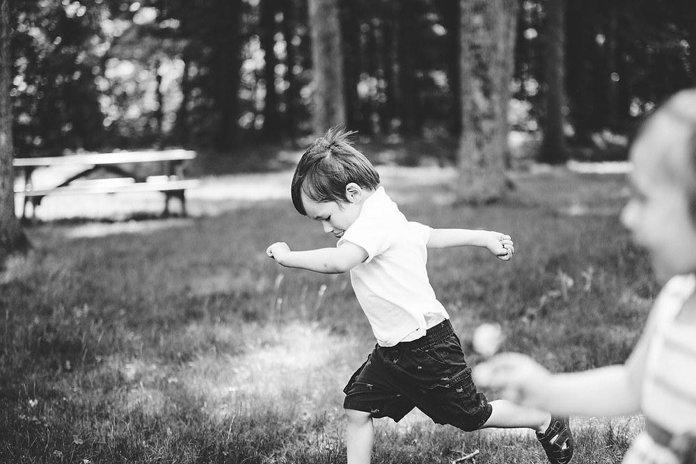 Little boy runs with his hands out looking at the ground in Connecticut