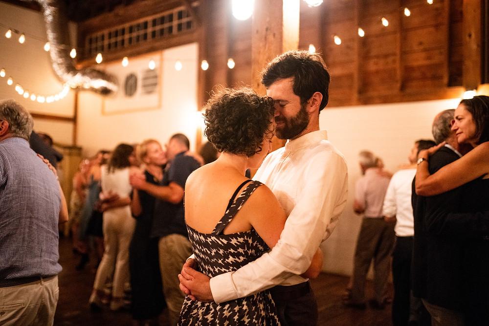 couple cuddles during wedding reception