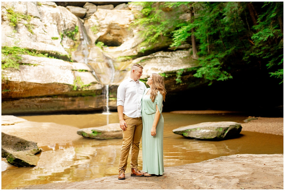 man and woman stand near waterfall at hocking hills state park