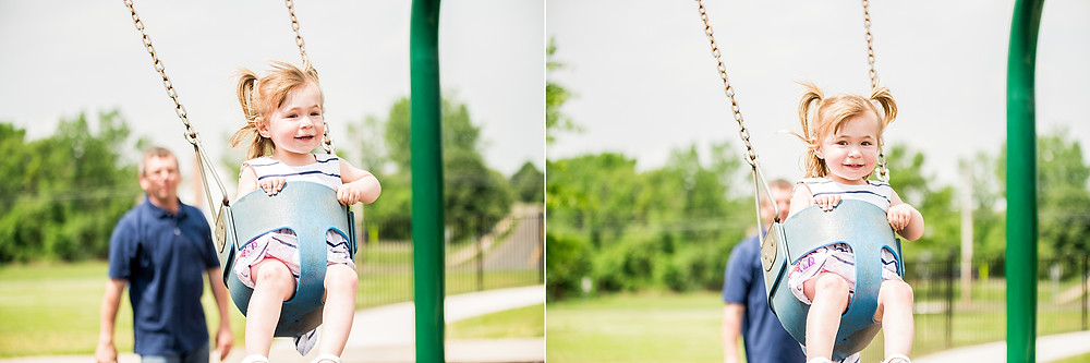 Dad pushes little girl in a swing as she smiles and laughs