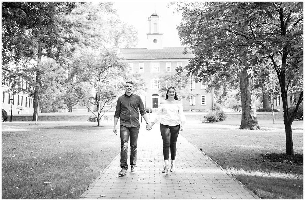 man and woman smile and walk on walkway at ohio university during engagement session