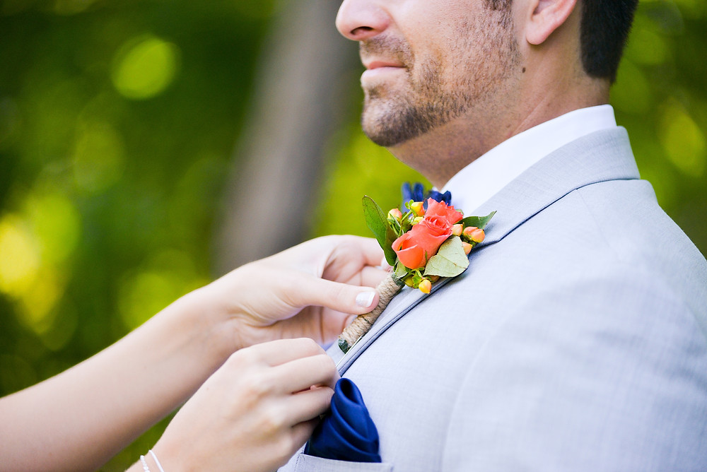 Bride places boutonniere on groom in Northeast Ohio