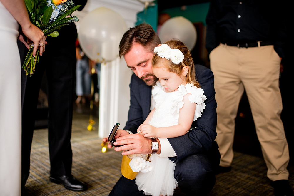 flower girl looks at necklace from dad at punch bowl social during wedding ceremony in cleveland ohio