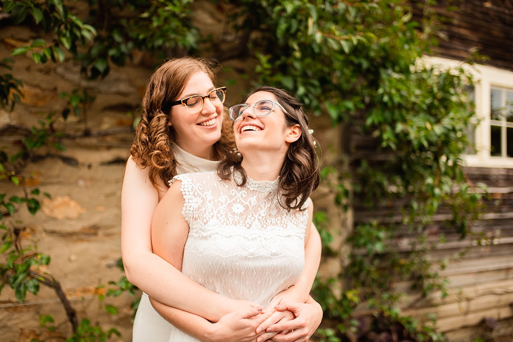 brides smile and embrace on their wedding day in front of a tree