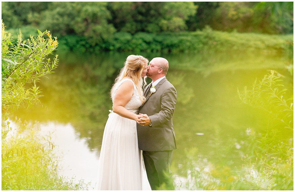 bride and groom kiss in front of lake