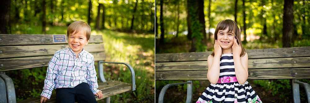 Little girl and boy sit on bench and smile in the forest.