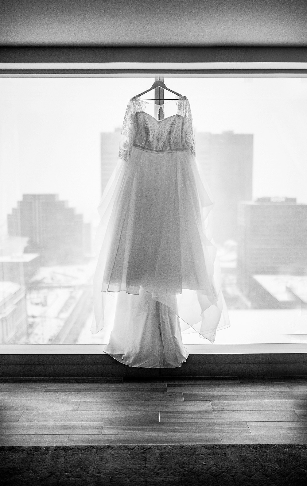 wedding dress hangs on window looking over the cleveland ohio skyline