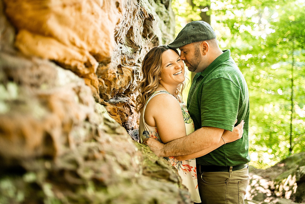 Man and woman hug and laugh against a rock at the Cleveland Metroparks
