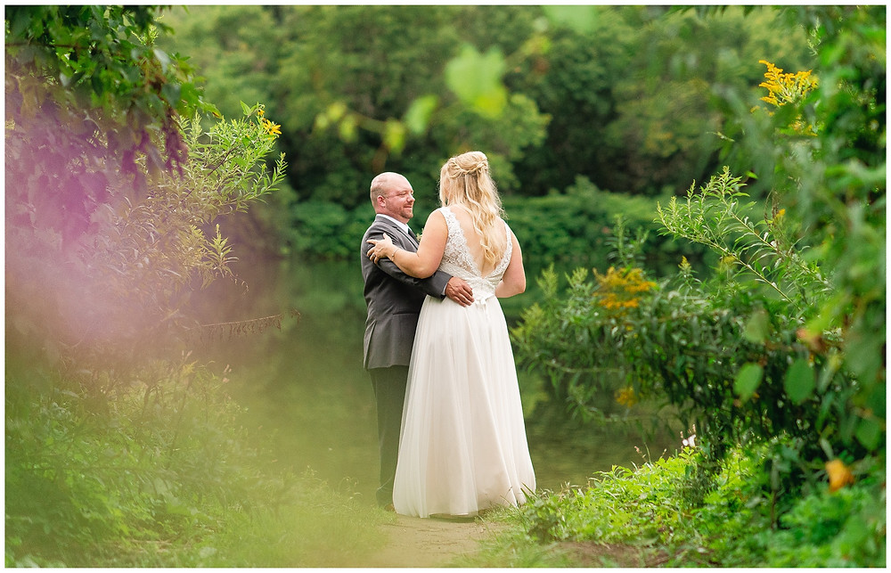 bride and groom dance in front of lake with colorful bokeh