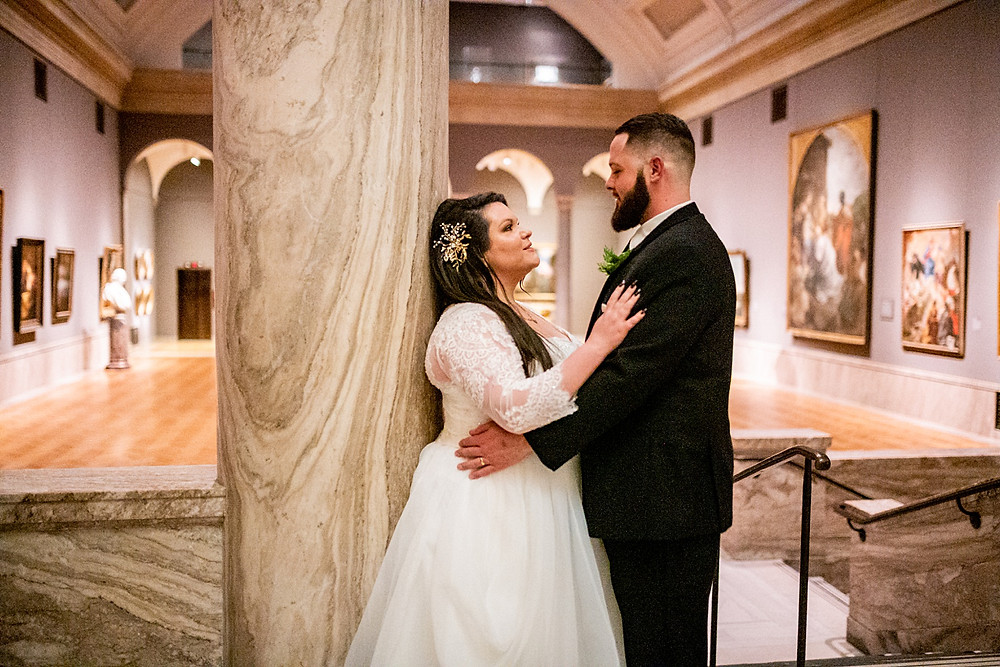 bride and groom embrace in gallery at the cleveland museum of art
