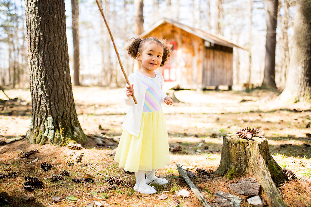 Little girl with a giant stick laughing