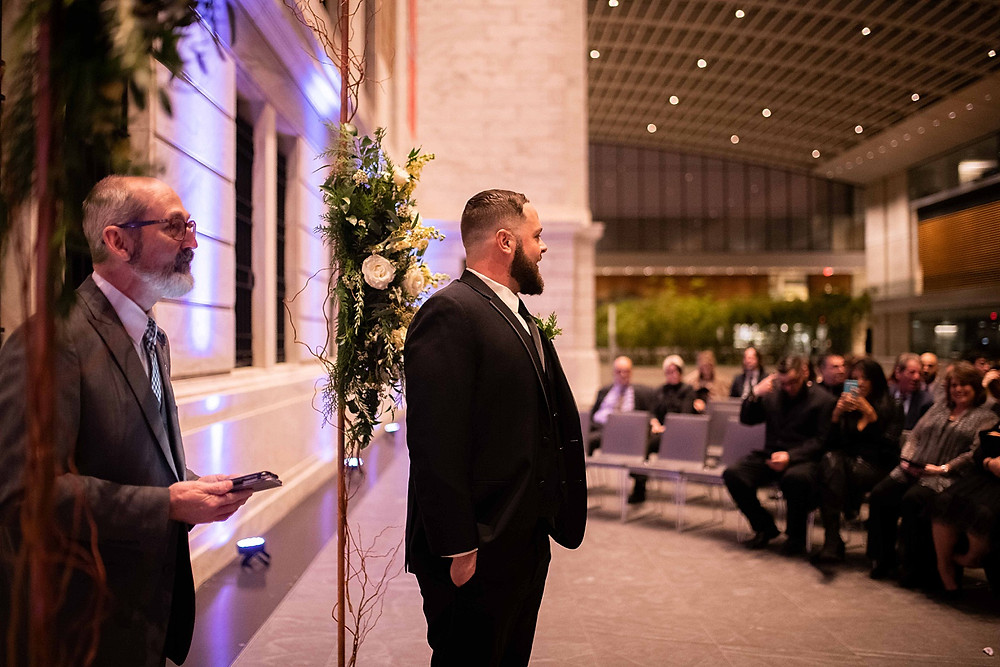 groom waits happily for his bride at the front of the aisle at the cleveland museum of art