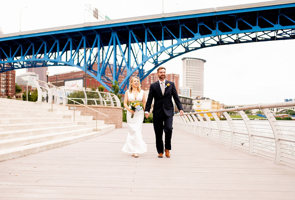 bride and groom stand in settler's landing park in the flats of cleveland ohio by cuyahoga river