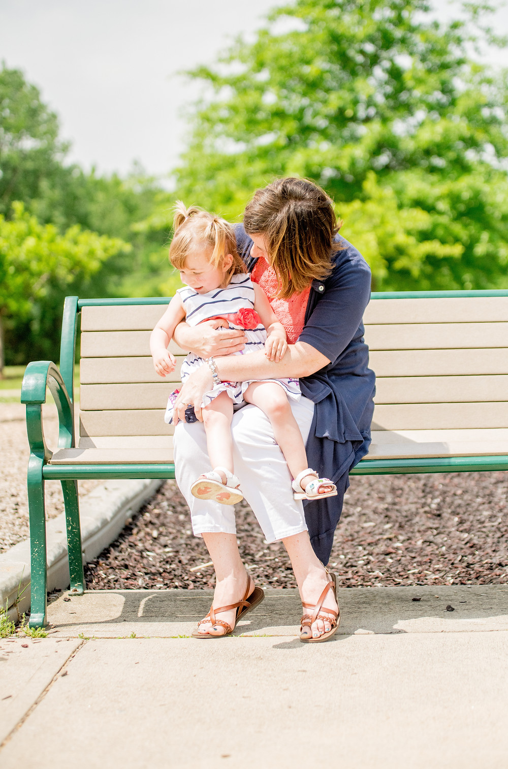 Mom and daughter cuddle sitting on a bench