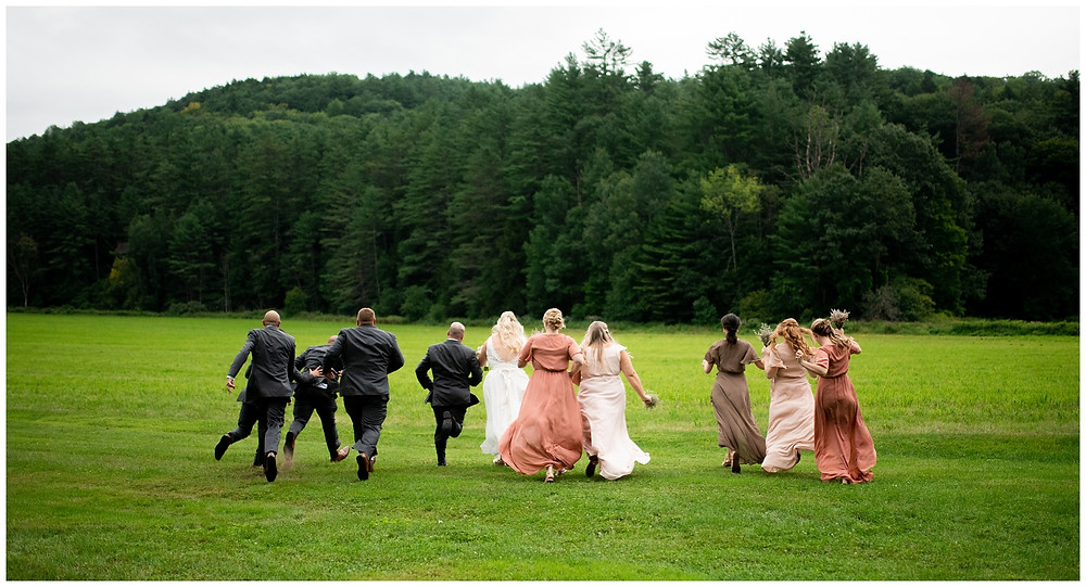 photo of bridal party running towards woods