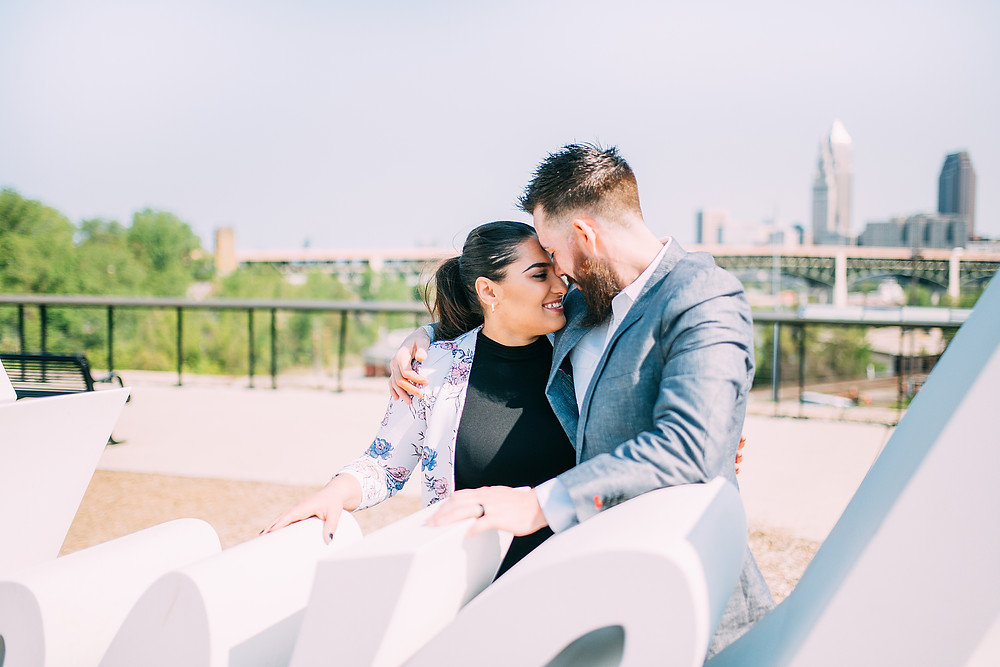 Man and woman stand close to one another with the Cleveland skyline in the background