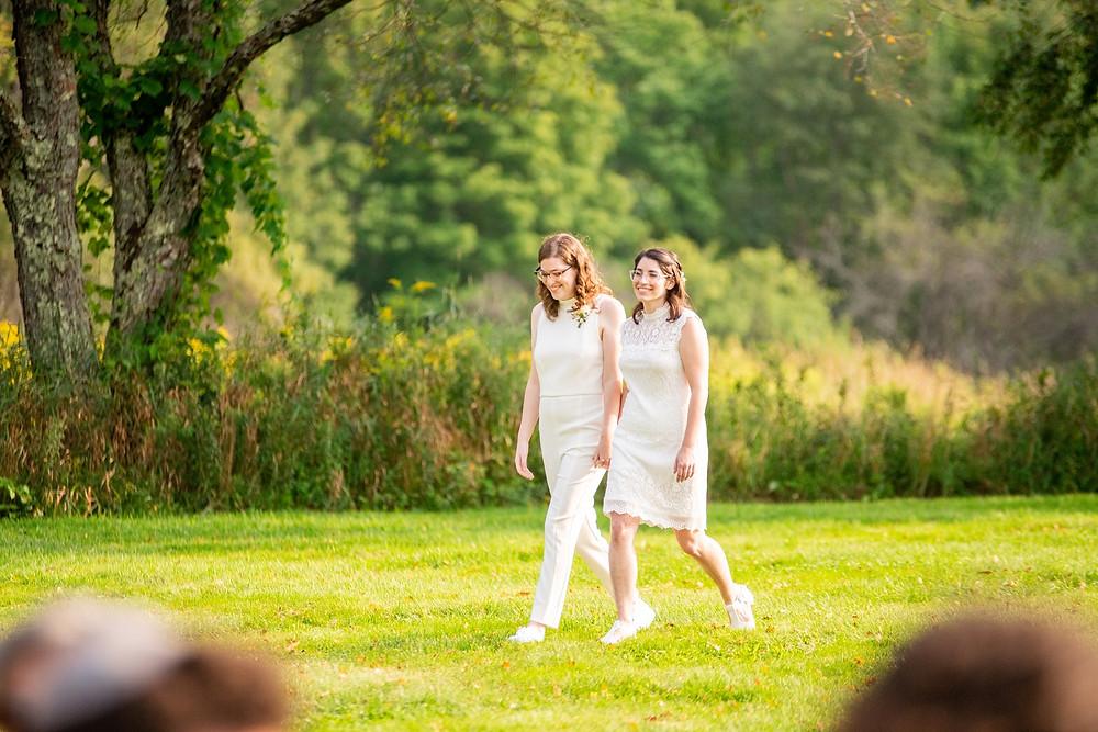 brides walk hand in hand on their wedding day