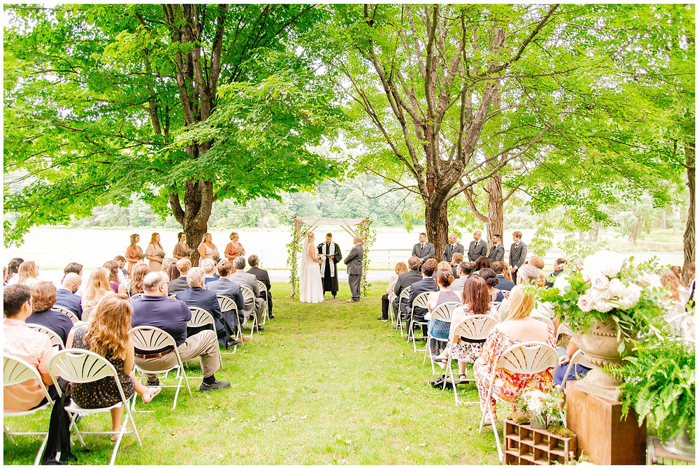 bride and groom stand and profess their love in wedding ceremony under trees