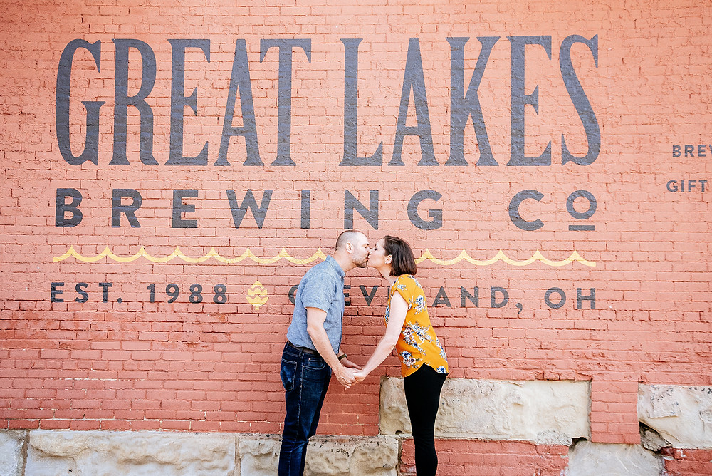 Man and wife hold hands outside of the great lakes brewing company mural
