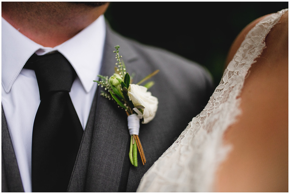 groom's boutonniere on his gray tuxedo