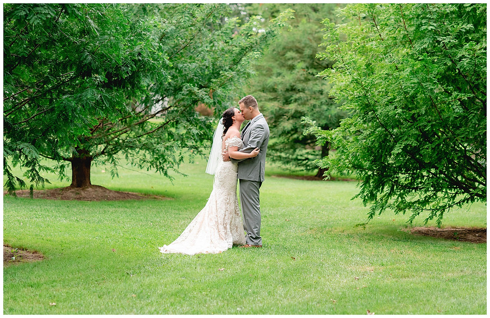 Bride and groom kiss on the campus lawn at Oberlin College