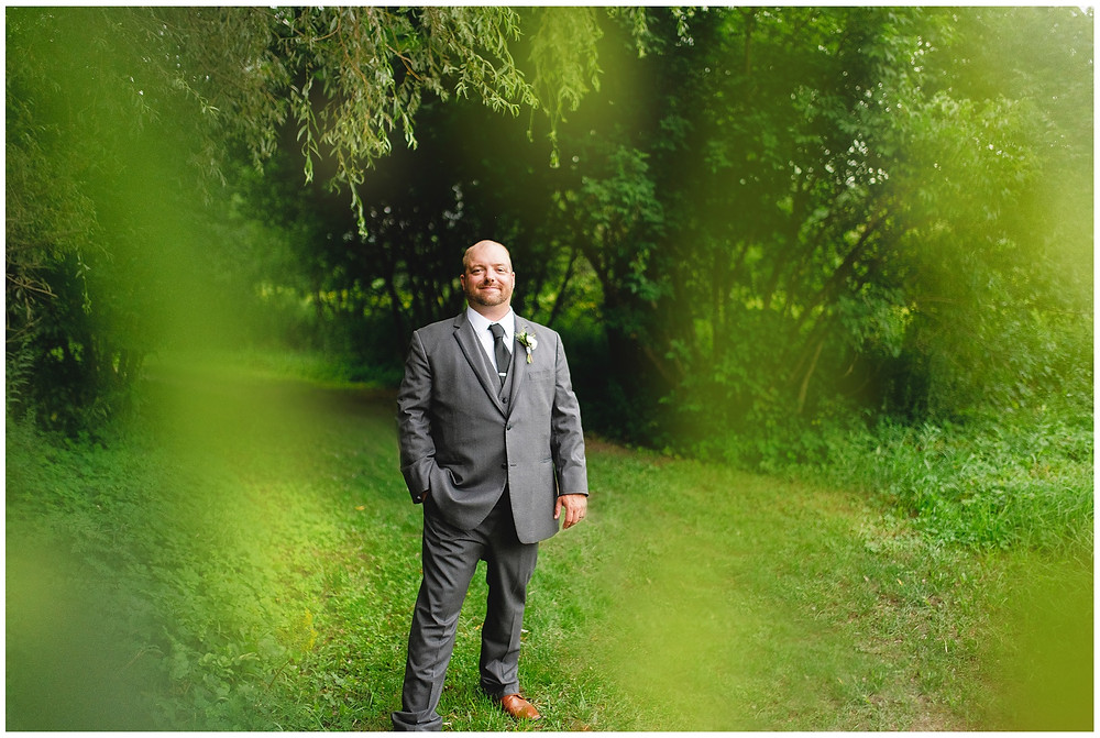 groom stands for portrait under the willow trees