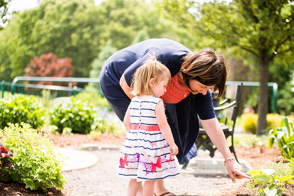 Little girl and her mom look at florals in a garden