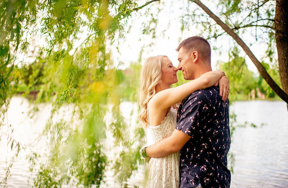 engaged couple eskimo kiss under weeping willow tree at gervasi vineyard