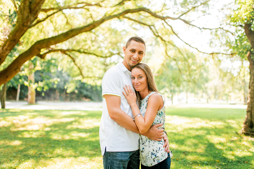 Man and woman hug under a tree at Wade Oval in Cleveland, Ohio