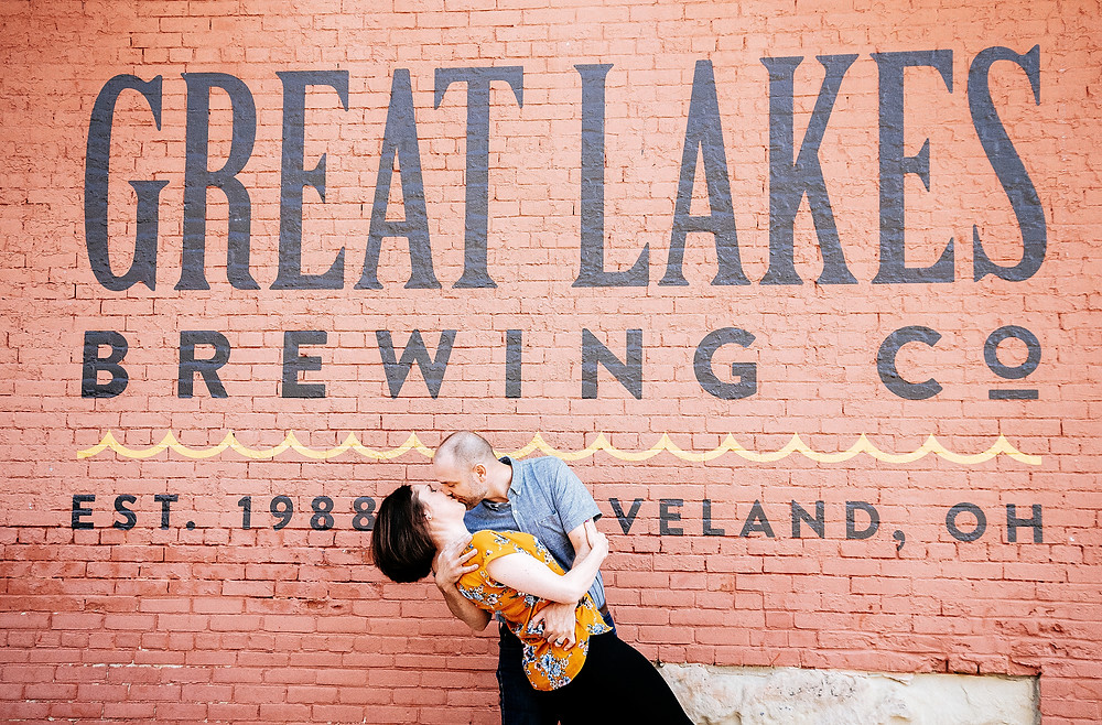 Husband and wife dip and kiss outside the Ohio City, Great Lakes Brewery mural