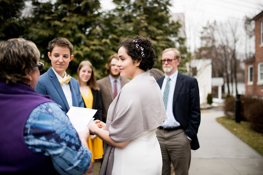 Bride looks at officiant during their wedding ceremony in Vermont