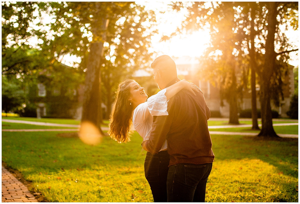 man and woman dance during engagement session on college green at ohio university during engagement session
