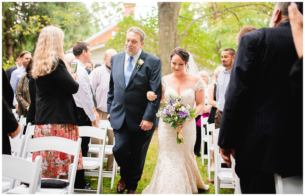 bride and her father walk down the aisle during outdoor ceremony near amherst Ohio