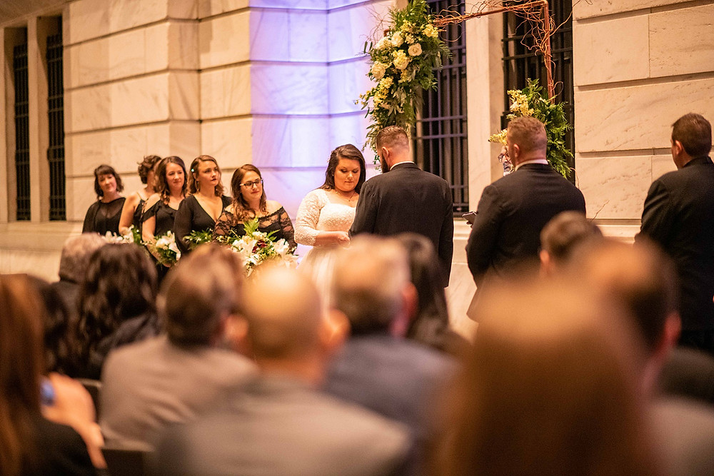bride and groom exchange wedding rings at the cleveland museum of art