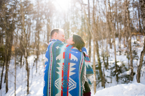 man and woman cuddling in the winter sunlight with a blanket