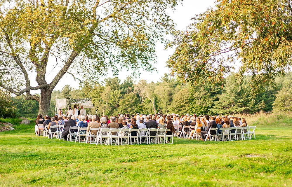 wedding ceremony in field surrounded by trees