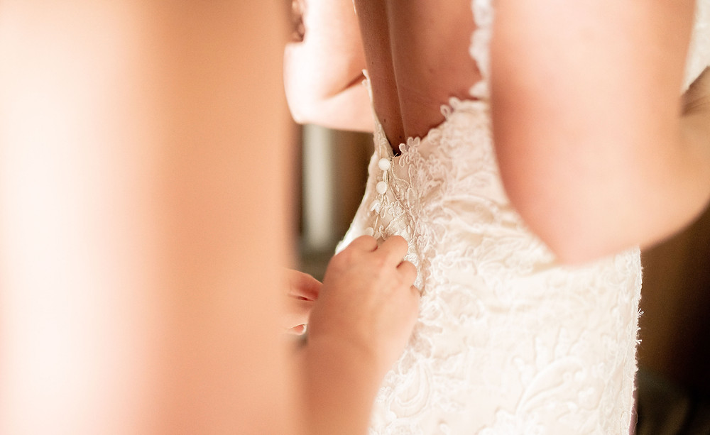 Bridesmaid helps bride button her wedding dress at a hotel near Cleveland, Ohio