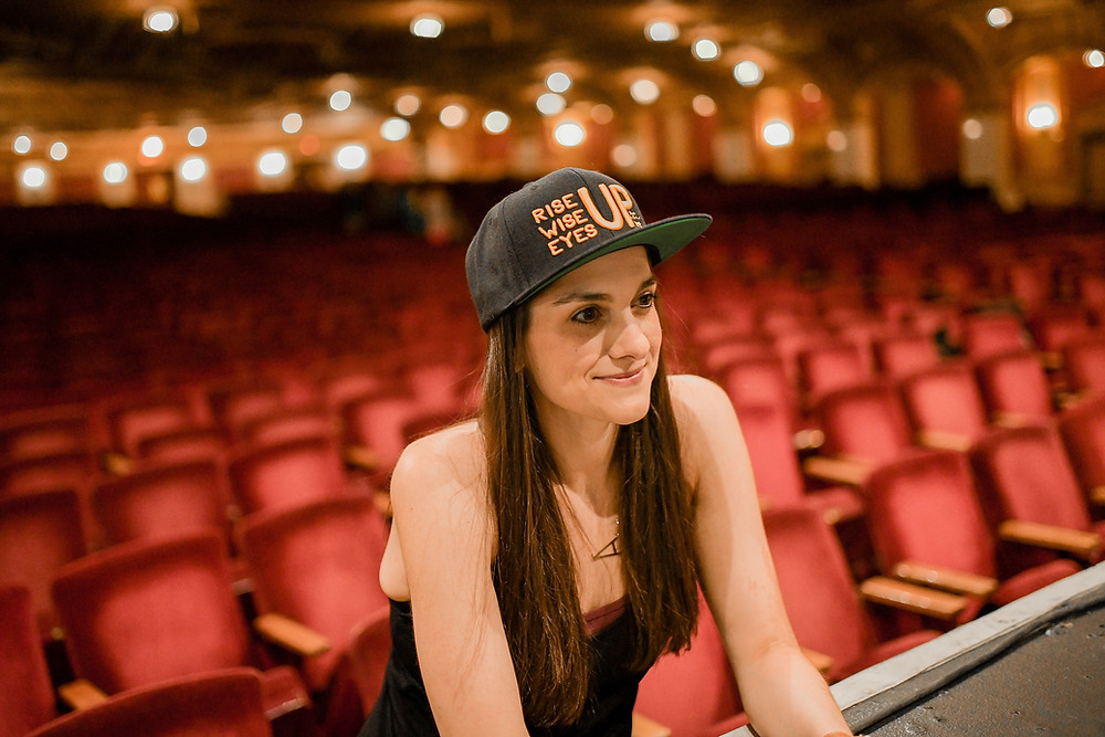 Woman in a baseball cap featuring a quote from Hamilton the Musical