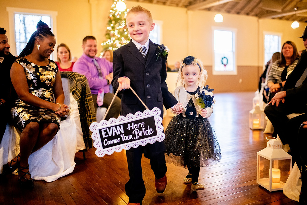 ring bearer and bridesmaid walk down the aisle at wedding in avon ohio