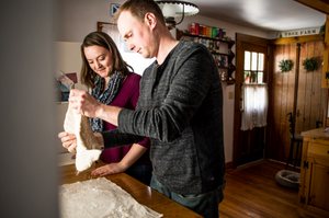 man is stretching out pizza dough as a woman watches in a kitchen
