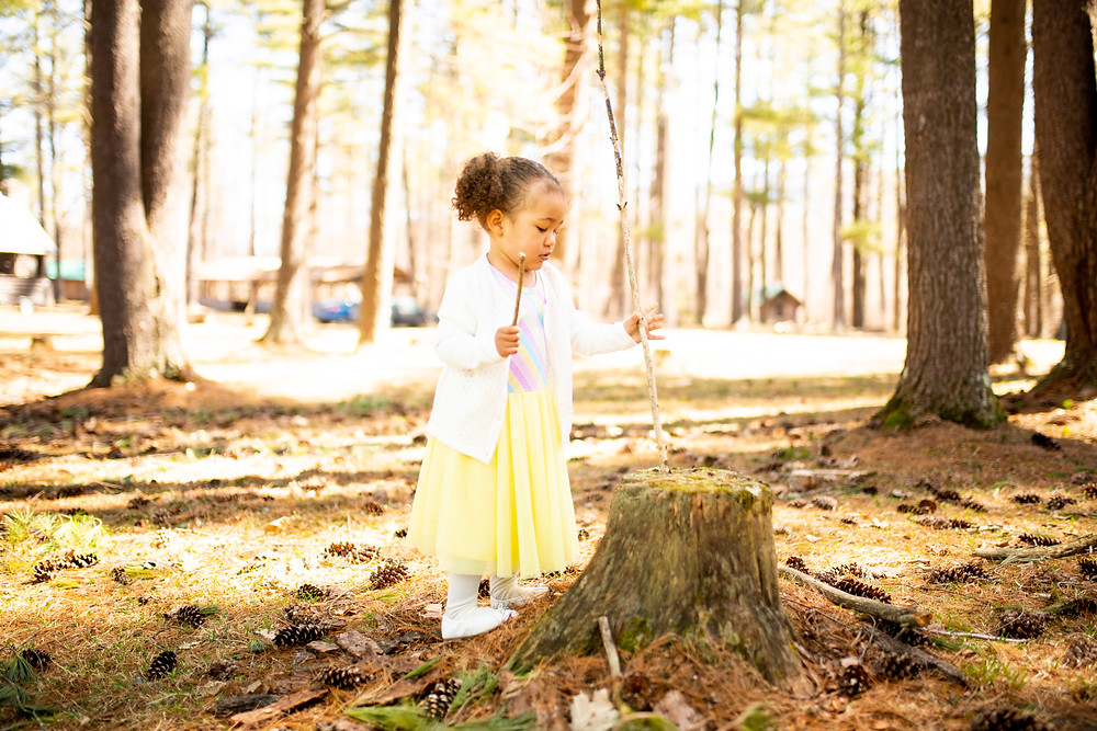 Little girl in yellow dress playing with a tree stump