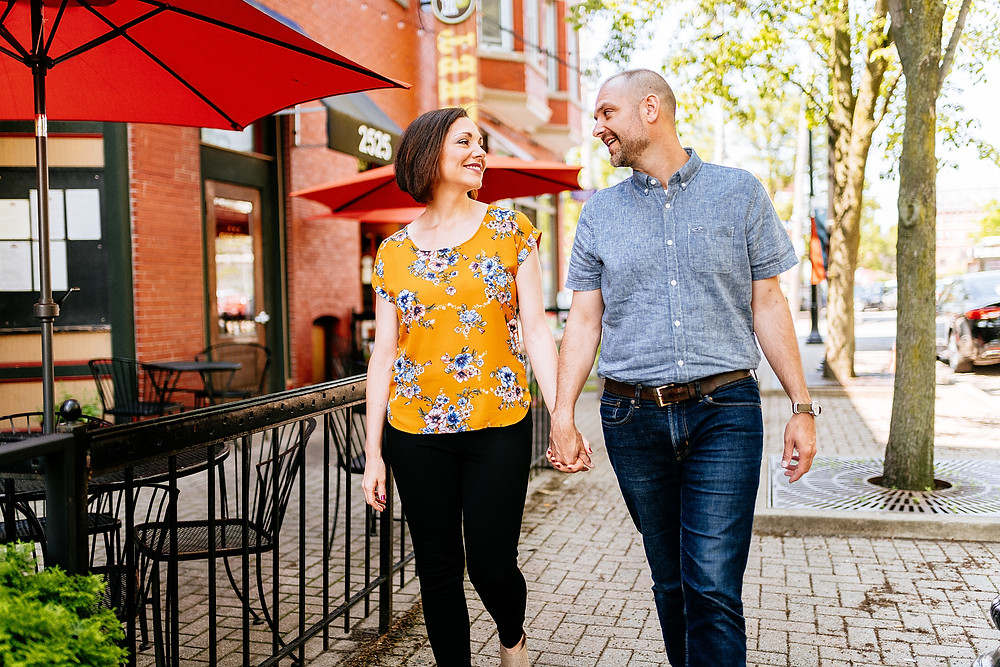 Husband and wife hold hands and walk down a brick street in Cleveland
