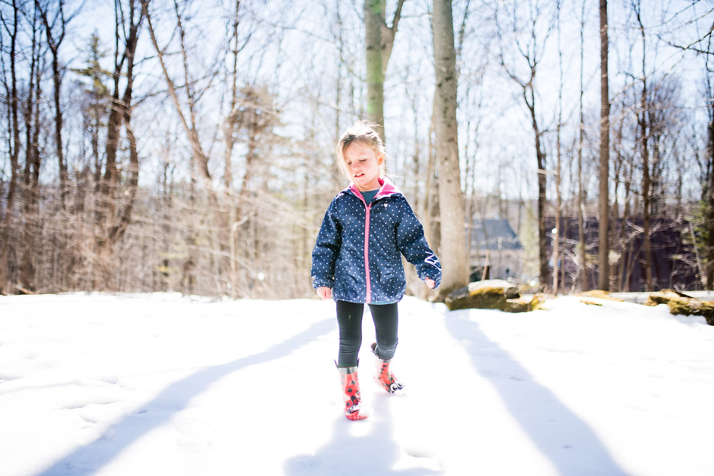 little girl walks in the snow with polka dot jacket