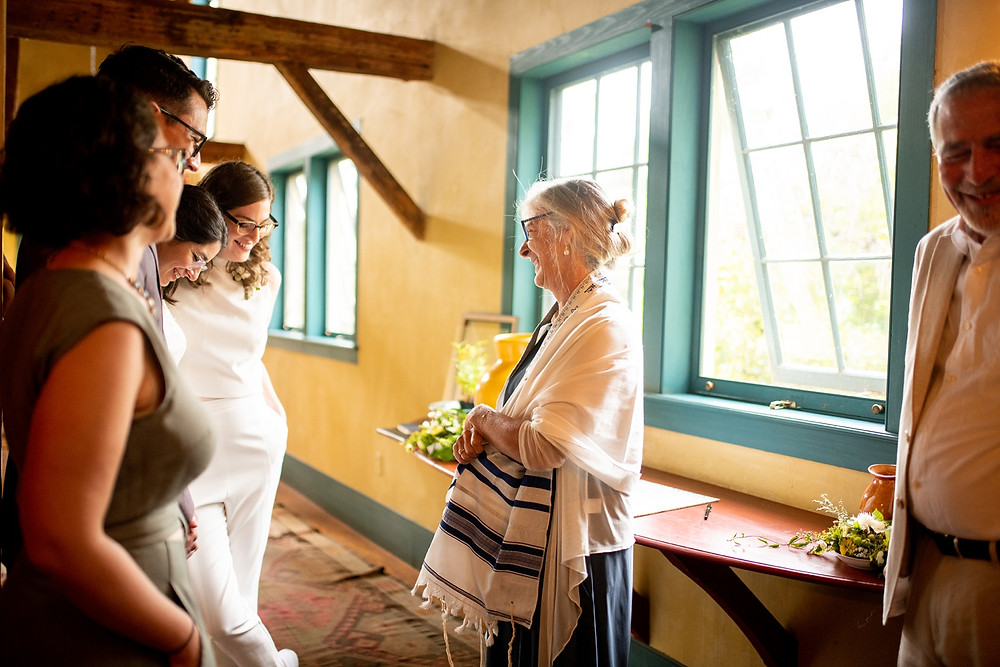 rabbi stands with brides on their wedding day
