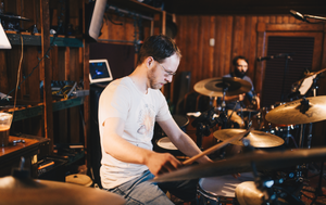 band member drumming on drum set in studio setting