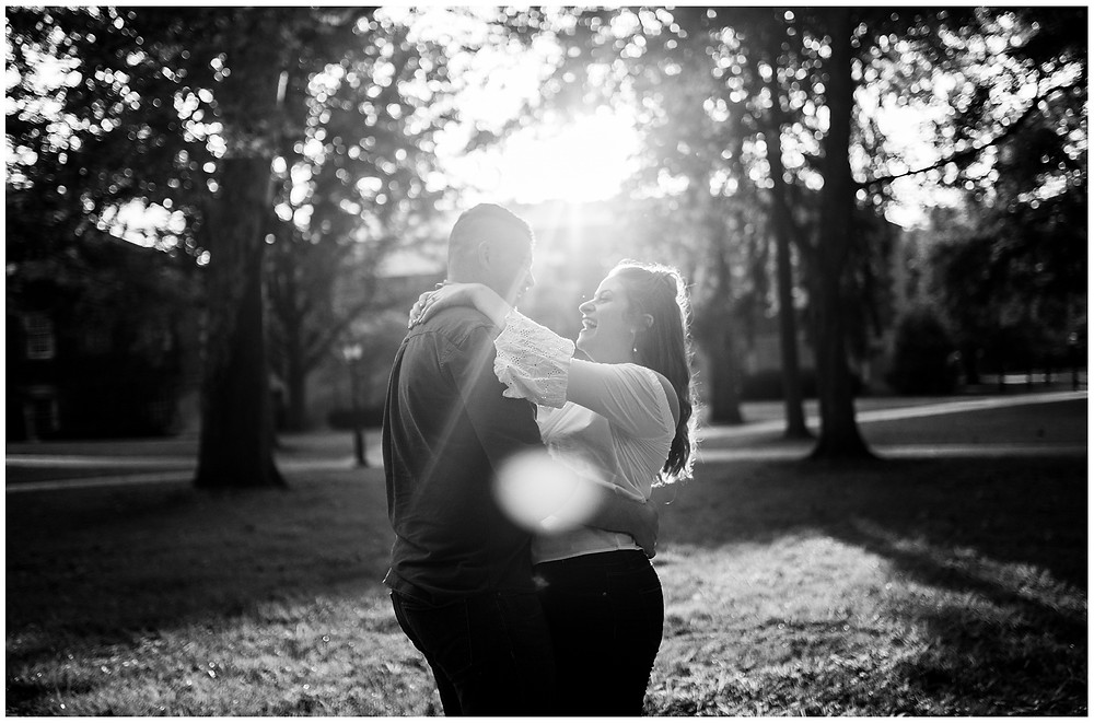 man and woman dance on college green during engagement session at ohio university