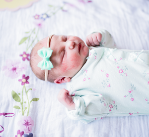 newborn baby wearing turquoise bow on her head