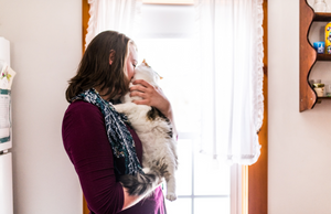 woman holding a cat near a window and nuzzling it with her face