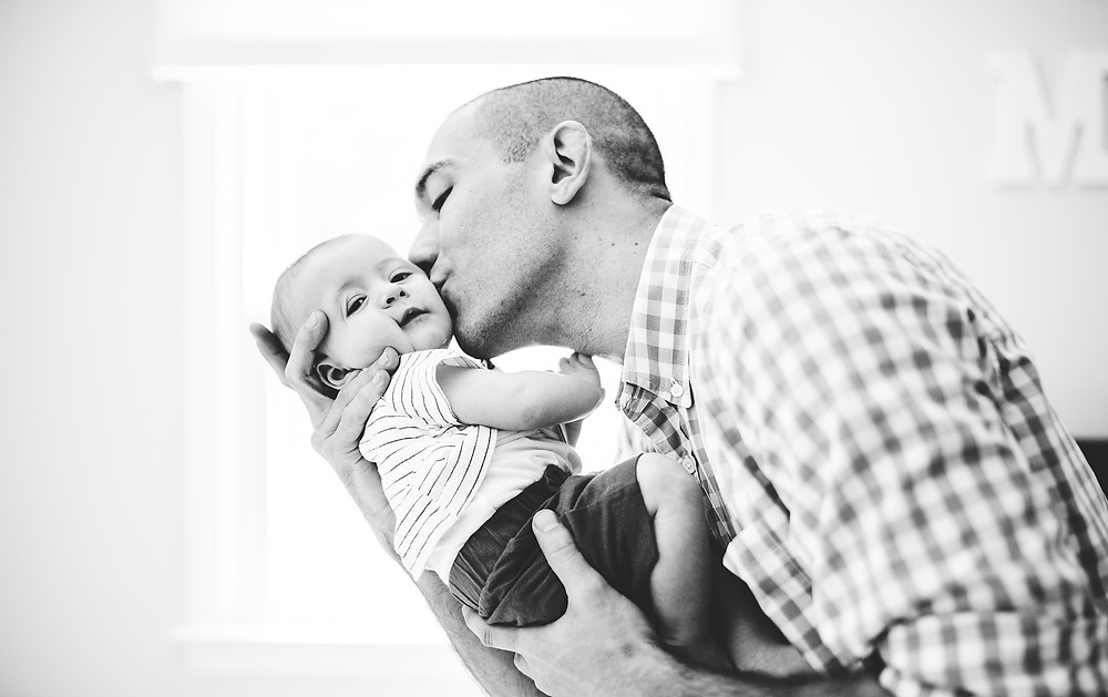 Dad snuggles and kisses baby in a nursery